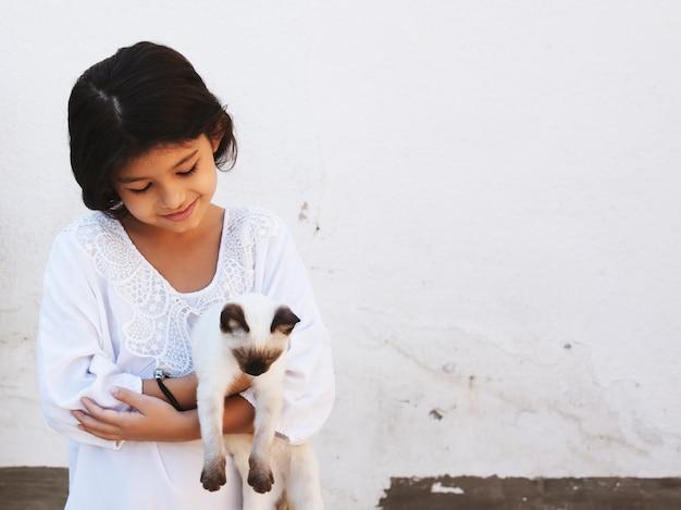 Милый парень девушка держит в руках красивый сиамский кот Premium Фотографии