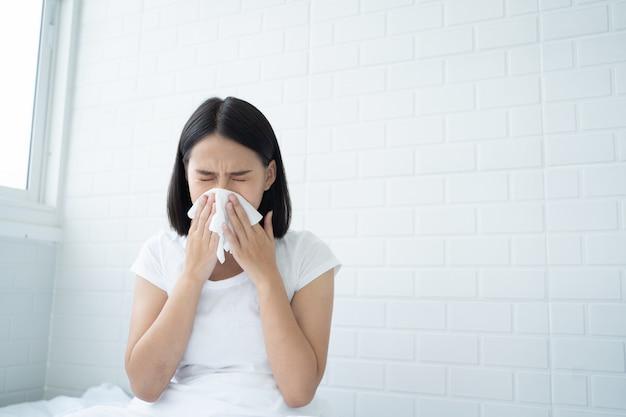 アジアの若い女性が鼻アレルギー、寝室のベッドに座って鼻くしゃみをするインフルエンザ Premium写真