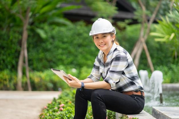 下水処理場でタブレットのラップトップで働くタイのアジアの女性工学 Premium写真