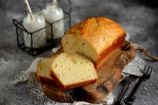 木の板に牛乳とおいしいオレンジケーキ。自家製のベーキング。 Premium写真