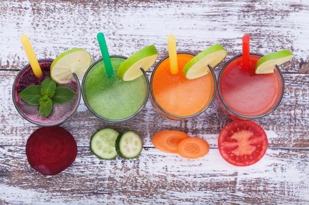 野菜、フレッシュジュースは、木のテーブルで果物の健康ドリンクをミックスします。 Premium写真