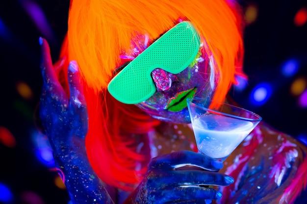 ネオンの光、ディスコナイトクラブでアルコールカクテルを飲むファッションモデルの女性。美しいダンサーモデルの女の子のカラフルな明るい蛍光メイク Premium写真