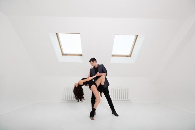 Красивая пара танцует бачата на белой комнате Premium Фотографии