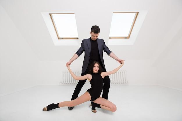 白い部屋でバチャータを踊る美しいカップル Premium写真