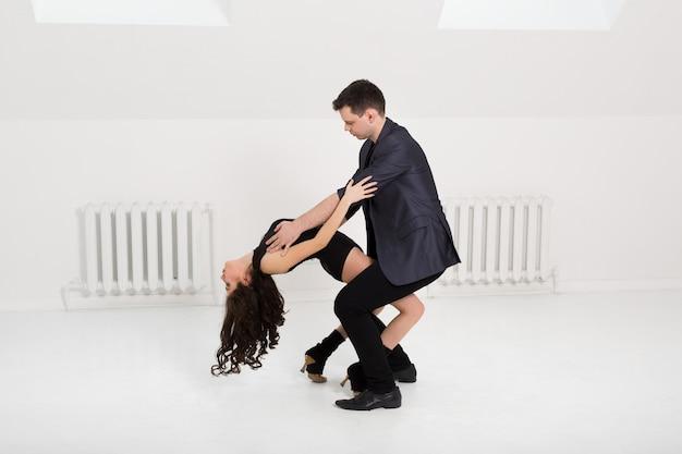 白い壁にバチャータを踊る美しいカップル Premium写真