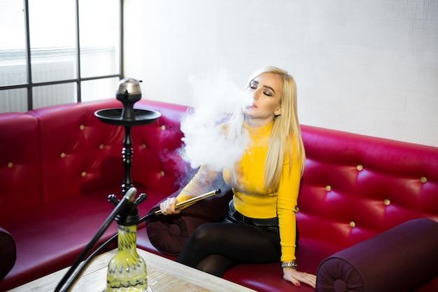 Красивая молодая женщина сидит на красном кожаном диване и курит кальян Premium Фотографии