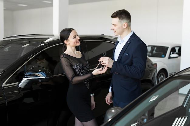 売り手は買い手にショールームの新車の鍵を与える Premium写真
