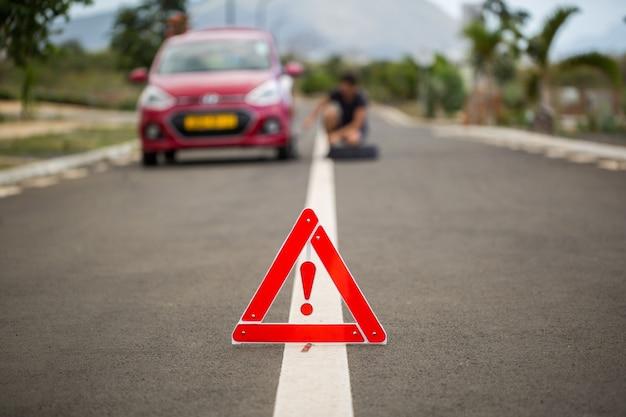男は故障した車に対してスペアタイヤを保持しています。 Premium写真