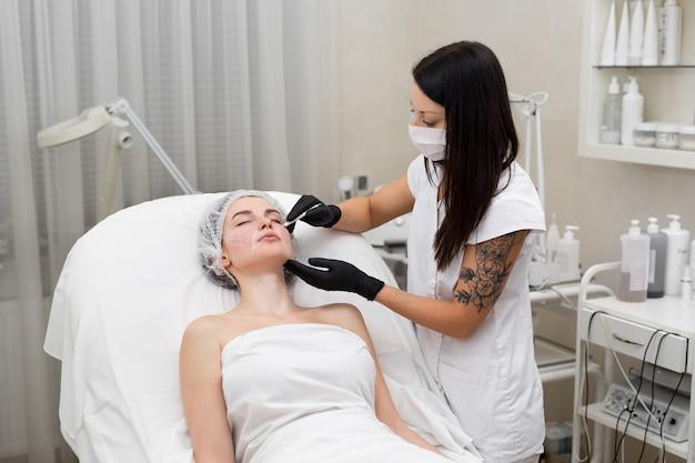 Косметолог рисует контуры белым карандашом на лице пациента. схематическая маркировка перед контурной обработкой. подготовка лица к косметической пластической операции крупным планом Premium Фотографии