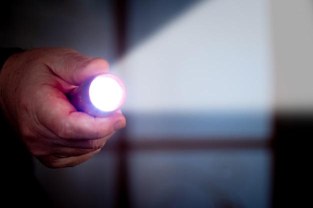男は暗い部屋で懐中電灯を持っています。他人の家への侵入 Premium写真