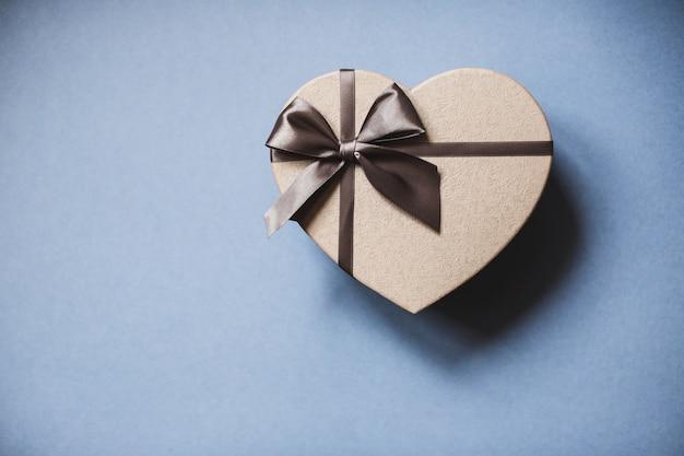 Подарочная коробка в форме сердца на синем фоне Premium Фотографии