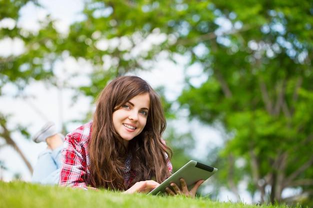 Молодая женщина с цифровым планшетом на траве Premium Фотографии
