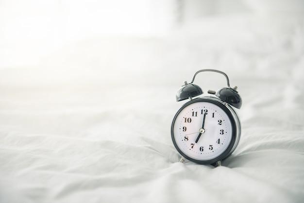 日光と朝のベッドの上の黒の目覚まし時計 Premium写真