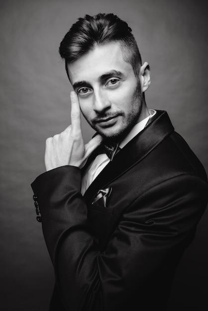 Фасонируйте портрет красивого элегантного человека при смокинг вьющиеся волосы нося представляя на серой предпосылке в студии. черно-белое фото Premium Фотографии