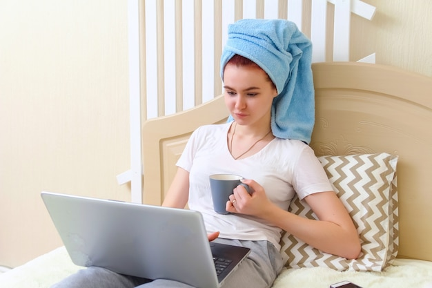 コンピューターで作業し、コーヒーを飲みながらベッドに座って彼女の頭にタオルで美しい少女 Premium写真