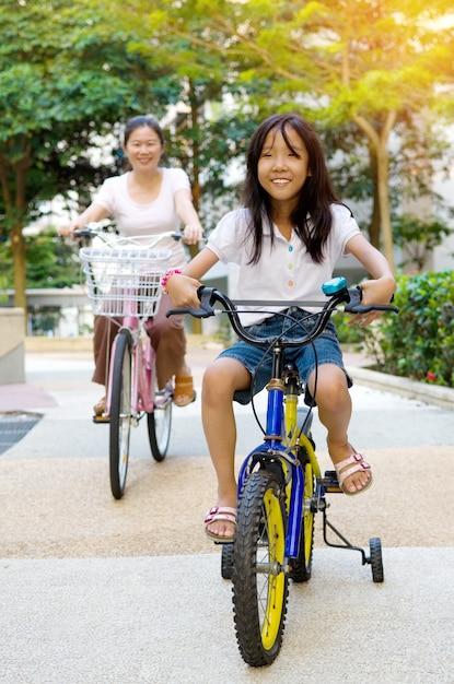 母と娘は公園で自転車をサイクリング Premium写真