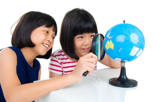 アジアの子供たちが地球を見て Premium写真