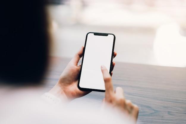 スマートフォンを保持している女性のクローズアップ、空白の画面のモックアップ。カフェで携帯電話を使用しています。 Premium写真