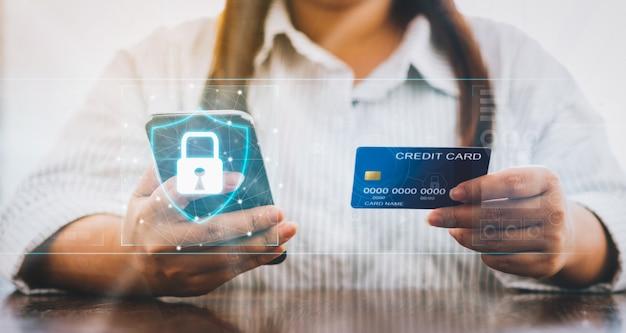 デジタルディスプレイに南京錠のアイコンが付いたスマートフォンとクレジットカードを保持している女性 Premium写真