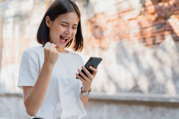 Женщина счастливых улыбок и проведение смарт-телефона с поражен успехом. Premium Фотографии