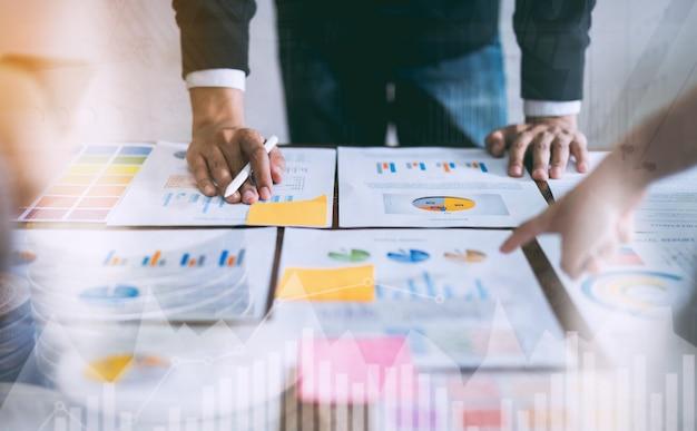 ビジネス人々会議チームの財務書類を指している木製の机と手マンに取り組んでいます。 Premium写真