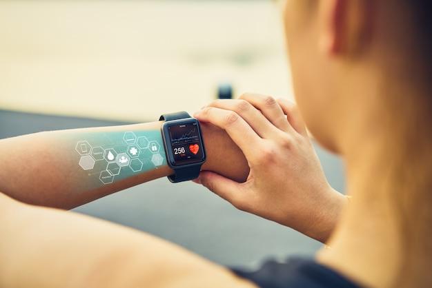 若い女性が画面のヘルスケアのアイコンとスポーツの腕時計をチェックします。 Premium写真