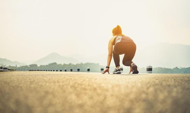 Женщина-бегунья на дорожных туфлях готовится покинуть исходную точку. Premium Фотографии