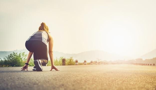 ロードシューズの女性ランナーは出発点を離れる準備ができています。 Premium写真