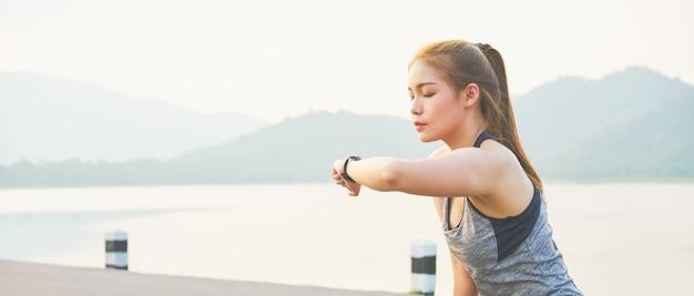 スポーツの腕時計を探していると彼女のパフォーマンスをチェックする若いアジア女性。路上で。 Premium写真