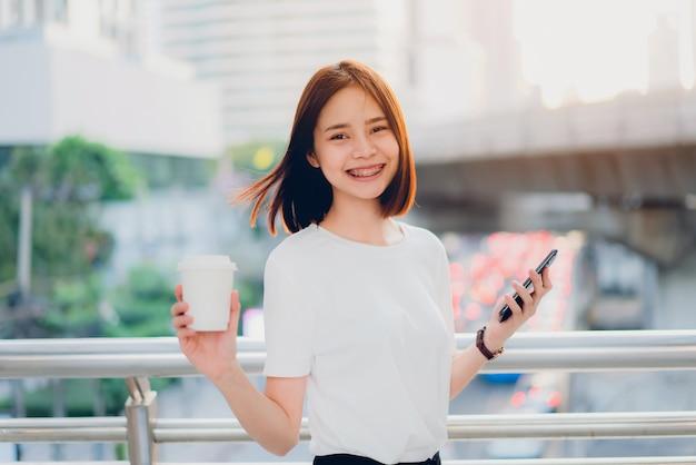 コーヒーカップを保持していると覆われた通路でスマートフォンを使用してアジアの女性の笑みを浮かべてください。 Premium写真