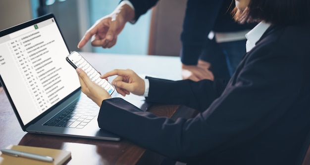 ノートパソコンとスマートフォンを使用してメール画面接続通信を読んで実業家。 Premium写真