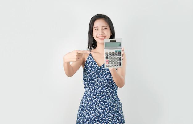 灰色の背景に分離されたアジア女性のポインティング指電卓を笑顔します。 Premium写真