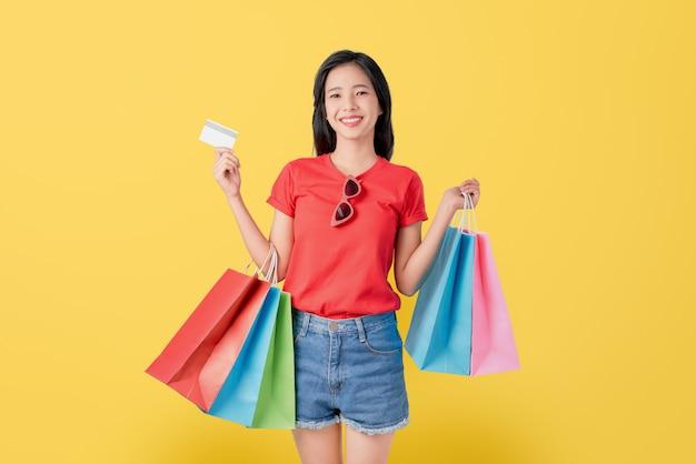 明るい黄色の背景に複数の色の買い物袋とクレジットカードを保持している陽気な美しいアジアの女性。 Premium写真