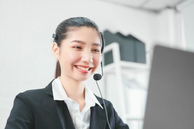 職場で顧客サポートの電話オペレーターのマイクヘッドセットを着て笑顔のアジア女性コンサルタント。 Premium写真