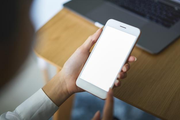 カフェのテーブルに空白の画面を持つスマートフォンを持っている手 Premium写真