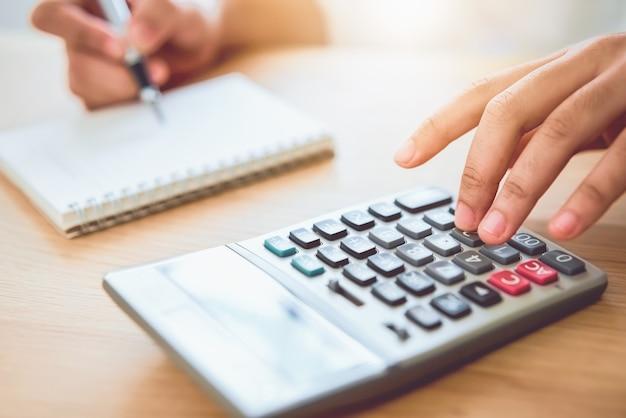 Удерживание женщины и калькулятор прессы для того чтобы вычислить расходы дохода и планы тратить деньги на домашнем офисе. Premium Фотографии
