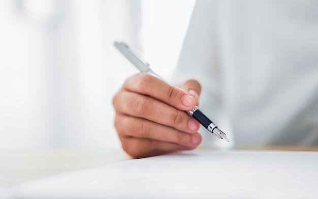 Крупным планом руки, держа перо и писать в блокноте Premium Фотографии