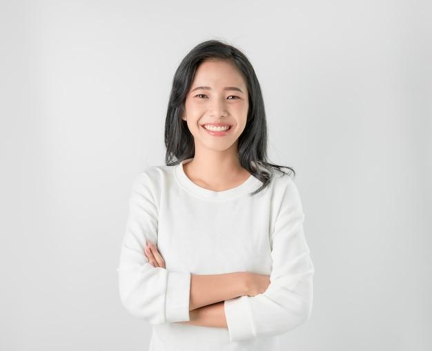 陽気な美しいアジアの女性が立ち、灰色の腕を組んだ。 Premium写真
