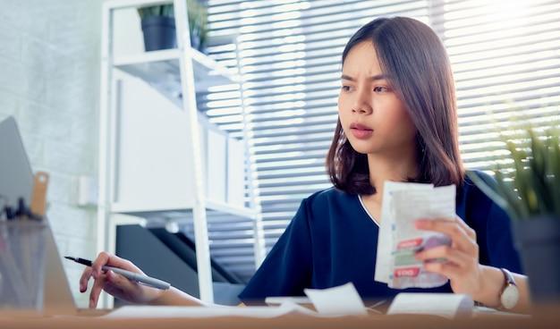 ホームオフィスのテーブルで毎月の経費請求書と債務請求書についての計算を保持している悲しいアジア女性の手。 Premium写真