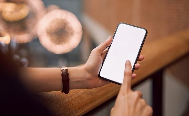 保持している女性とモールでスマートフォンの空白の画面をタッチします。画面を見て広告を出します。 Premium写真