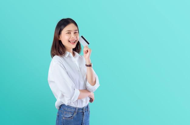 組んだ腕を持つ空白のクレジットカードを保持している若い笑顔のアジア女性 Premium写真