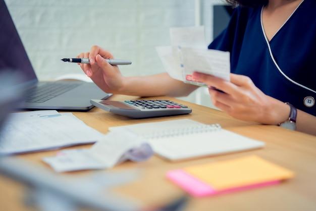 Рука женщины держа счет счета и расчет о счетах задолженности ежемесячно на таблице в домашнем офисе. Premium Фотографии