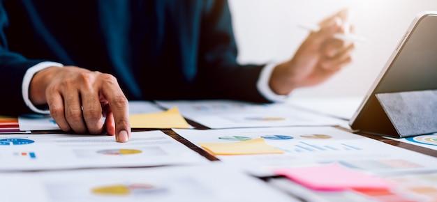 デジタルマーケティング、オフィスデスクの背景にデジタルタブレットとドキュメントを使用するビジネスマン。 Premium写真