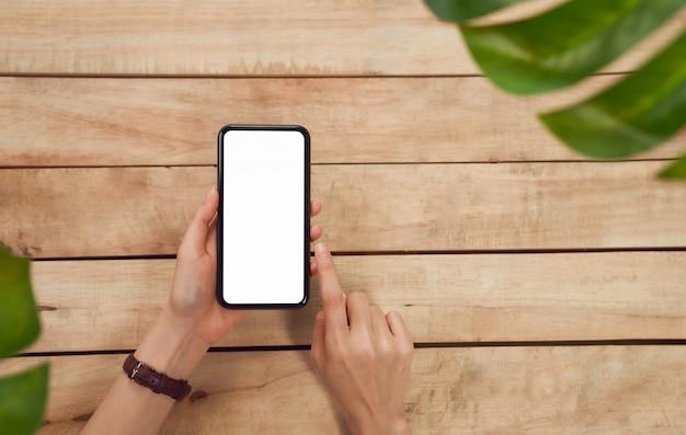 女性の手がスマートフォンを押し、木製のテーブルに空白の画面を押すと、あなたの広告を取る。通信コンセプトの技術。 Premium写真