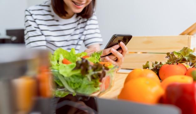 自宅のテーブルにトマトと様々な緑の葉野菜のスマートフォンとサラダボウルを持つ女性の手は、あなたの広告を取る。 Premium写真