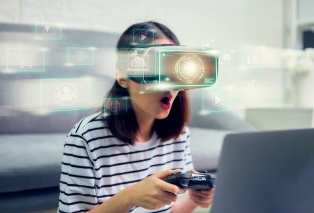 デジタルテクノロジーの概念の接続とインターフェイス、仮想現実のヘッドセットとジョイスティックを使用して興奮した若いアジアの女性、色の線で美しい光。 Premium写真