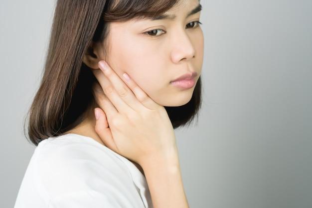 Азиатская девушка в белом случайном платье поймает это плечо, из-за боли тяжелой работы. Premium Фотографии