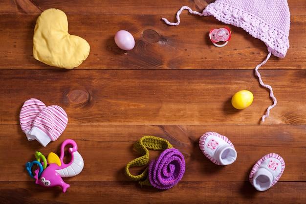 Комплект детской одежды, вязаная хлопковая одежда, детские игрушки на коричневом деревянном столе Premium Фотографии