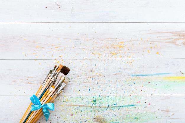 水しぶき、芸術的なキャンバスの背景、絵画のための創造的なスペース、画家の職場、子供キッズアートデスク、コピースペースの平面図と白い木製の塗られた染色テーブルにペイントブラシセット Premium写真