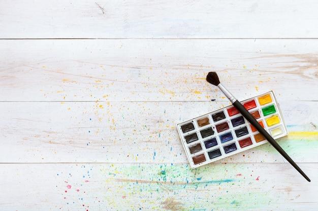 学習の絵画の概念、ペイントブラシ、水しぶき、芸術の背景、子供たちの創造的なアートの職場、コピースペース、フラットレイアウトの平面図と白い木製のテーブルに水彩絵の具でボックス Premium写真